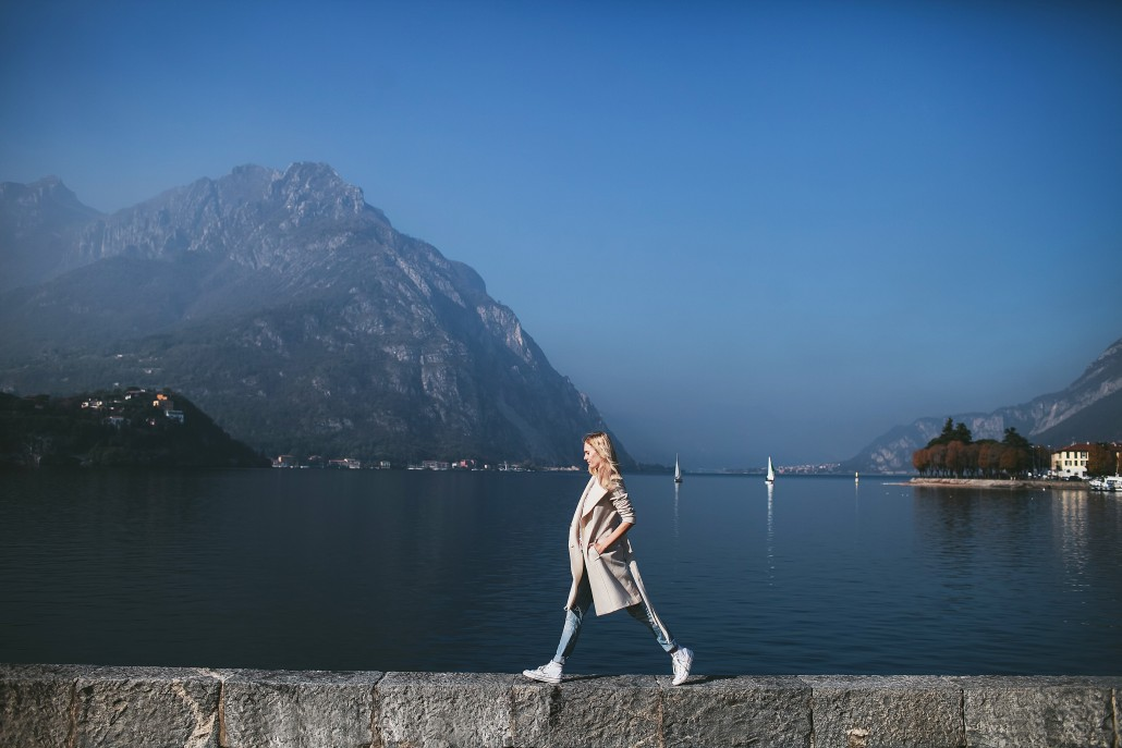 blond woman in coat standing against the background of a mountain lake Como